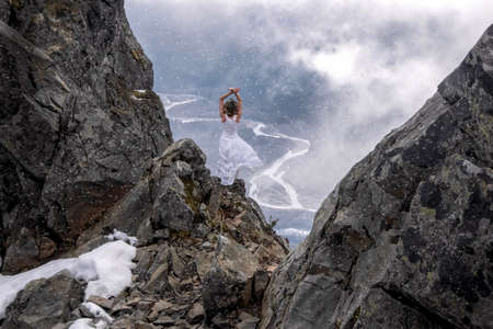 Woman in white dress standing on the edge  of a steep rock with a river view in clouds in a snow storm. First snow storm in North Cascades National Park. Concrete. Washington State. United States of America.