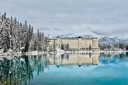 Chalet de montagne dans la forêt d'hiver au bord d'un lac alpin turquoise et calme avec des montagnes enneigées derrière. Magnifiques reflets d'hôtel à Lake Louise. albertaine. Canada