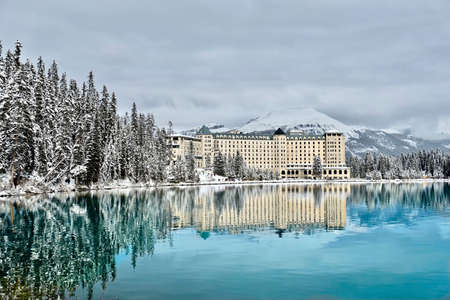 Mountain lodge in winter forest by turquoise calm alpine lake with snow capped mountains behind it. Gorgeous reflections of hotel in Lake Louise. Alberta. Canada