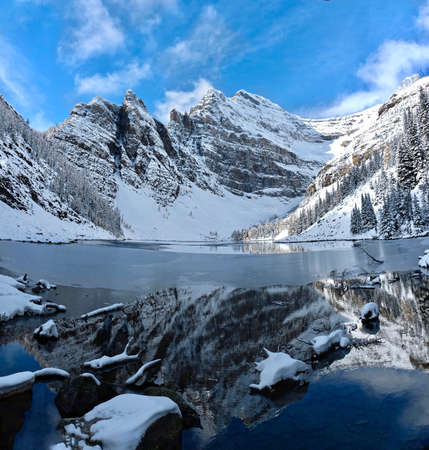 Lake Agnes and mountains around covered with first fresh snow.  Early winter panorama of the lake and reflections of rocks on lake shore. Lake Louise area near Big Beehive hiking trail. Banff.  Alberta. Canada. Фото со стока