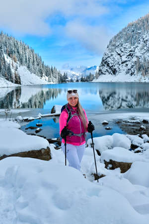 Pretty smiling woman in sporty clothes backcountry skiing in Lake Louise area on a clear winter day. Tea House at lake Agnes. Banff National Park. Alberta. Canada Stock Photo