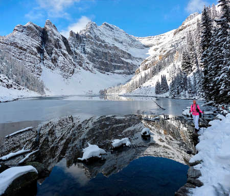 Winter vacation in Canada. Happy smiling woman  snowshoeing in Banff National Park near alpine lake surrounded by mountains. Fresh snow in Canadian Rocky Mountains in Lake Louise area. Alberta. Canada Фото со стока