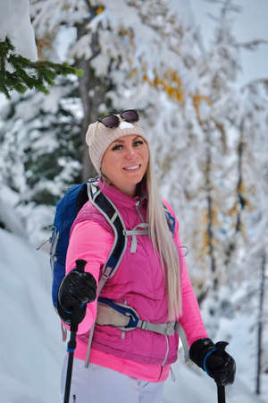 Portrait of a young smiling active woman with green eyes in winter sporty clothes hiking in snowy forest.  Canadian Rockies. Banff National park.  Lake Louise area. Alberta. Canada Фото со стока