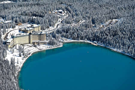 Lake Louise resort in Canadian Rockies. Blue alpine lake with boats and forest covered with fresh snow. Banff National Park. Alberta. Canada
