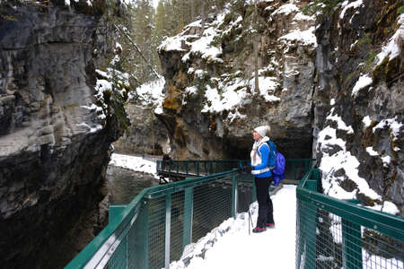 Young woman hiking in Johnston Canyon in winter. Canadian Rockies. Banff National Park. Alberta. Canada