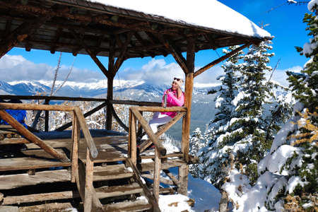 Happy smiling woman in ski clothes drinking tea in open veranda on mountain top with expansive views. Winter ski resort in Canadian Rockies. Lake Louise area. Alberta. Canada
