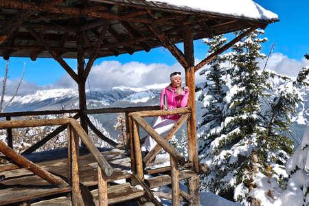 Young blond woman skier drinking tea on mountain top veranda.  Winter in Canadian Rockies. Lake Louise ski resort. Alberta. Canada