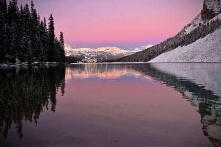 Pink sunrise over alpine lake mountain resort. Lake Louise chateau reflection in calm water. Banff National Park. Alberta. Canada