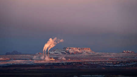 Smoking industrial chimneys in red desert in sunset. Power plant near Page. Arizona. United States of America