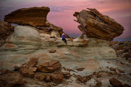 Woman tourist sitting on rock watching sunset.  Giant toadstool rocks near Lake Powell in Arizona at sunset. Winter travel to Southwest of United States of America Фото со стока