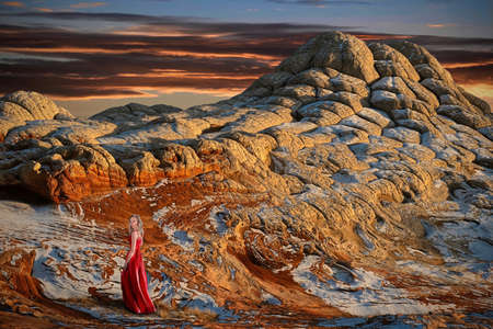 Young blond woman in red dress walking on colorful rock desert at sunset. Vermillion Cliffs National Monument, White Pocket near Page. Arizona. United States of America Zdjęcie Seryjne