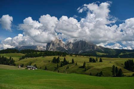Dolomites Mountain range landscape with alpine meadows, sharp rocks and little hut refuge. Alpe di Siusi. Kanazei. South Tyrol. Italy