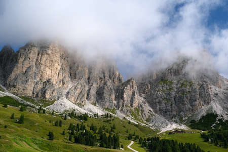 Scenic view of mountains with light clouds and alpine meadows in Dolomites. Selva di Val Gardena Pass. South Tyrol. Italy