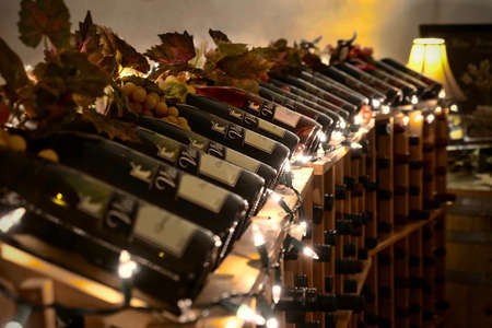 SALEM, OREGON/USA - November 10, 2019: Bottles of wine in a stand in Vitis Ridge Winery with Christmas lights and grapes.