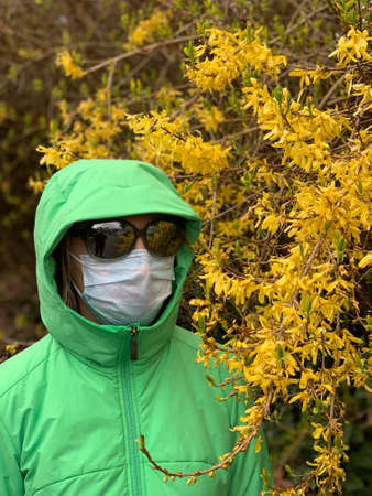 Woman in face protective mask and glasses near the blossom tree. Portrait. Vancouver. BC. Canada. Фото со стока