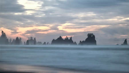 Sea stacks in the ocean at sunset with salty mist from the ocean. Shi Shi Beach. peninsula. Washington State. United States of America