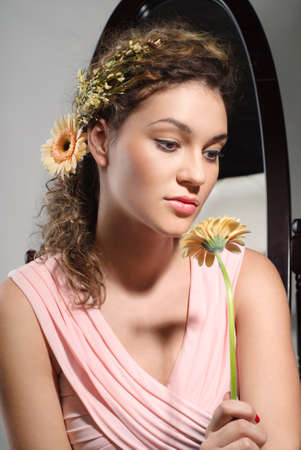 feminity: Young beautiful girl is holding a flower  Studio portrait Stock Photo