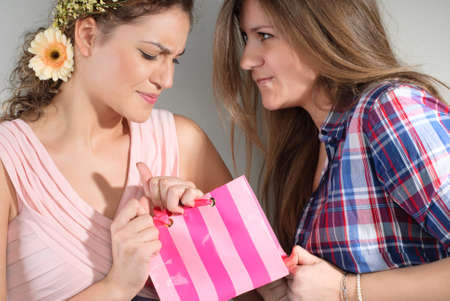 strife: Two funny beautiful girls is holding plastic pink bag