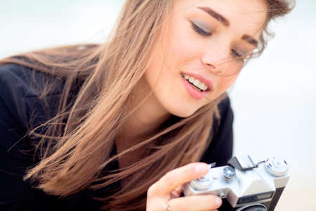Beautiful young girl is holding old film camera