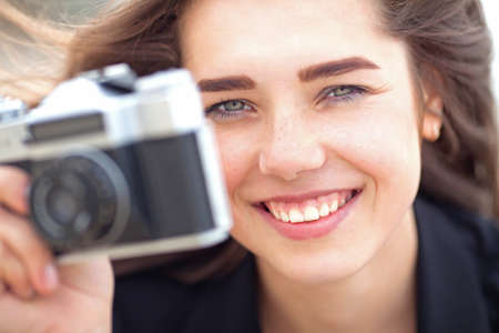bashful: Beautiful young girl is holding old film camera