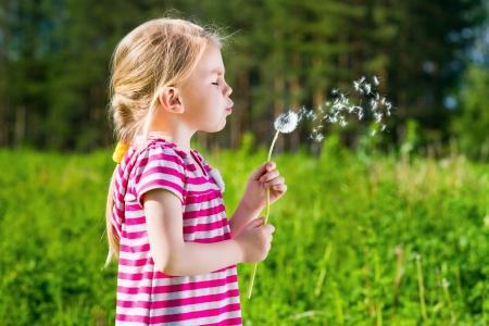 Blond little girl blowing a dandelion Фото со стока