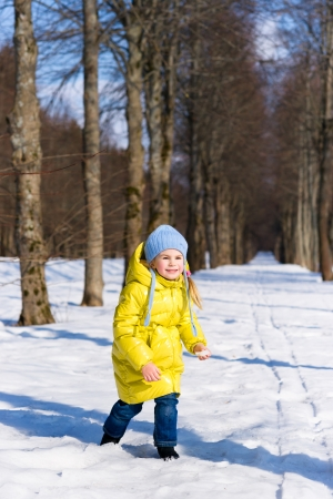 yellow jacket: Funny little girl playing in winter
