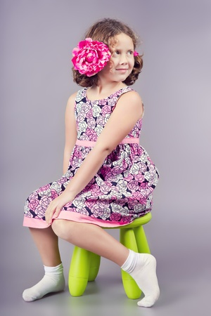 white socks: Cute girl in pink sitting on a green chair Stock Photo