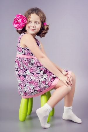 Beautiful girl in pink sitting on a green chair Banque d'images