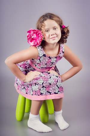 Adorable girl in pink sitting on a green chair photo