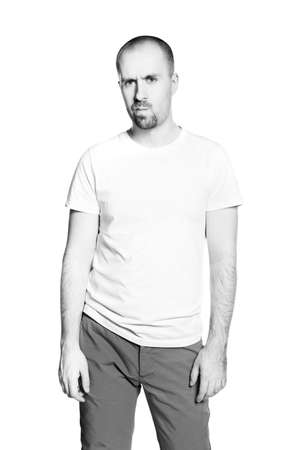 Black and white portrait of a disappointed young man in white t-shirt isolated on white photo