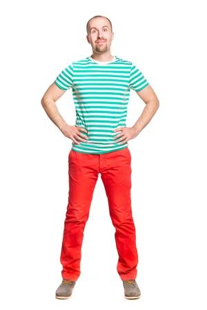 hombre calvo: Hombre joven alegre que sonríe con los ojos bien abiertos en los pantalones vaqueros blancos y turquesa camiseta naranja y rayas aislado en blanco