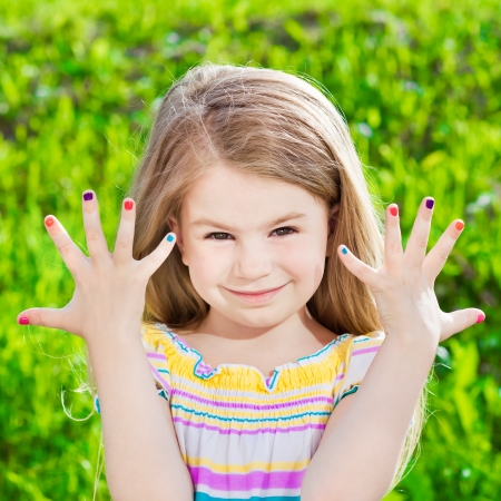 Cute smiling blond little girl with many-coloured manicure Banque d'images