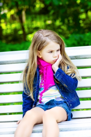 Sad blond little girl sitting on a bench in the park photo