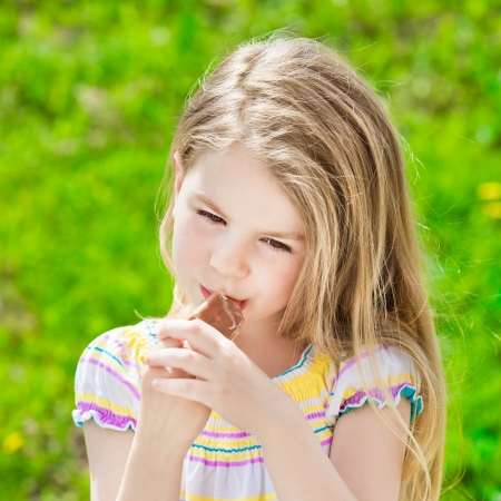 Adorable blond little girl with long hair eating ice-cream in summer sunny day