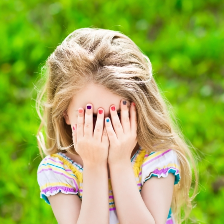 little blonde girl: Beautiful smiling blond little girl with long hair and many-coloured manicure covering her eyes with her hands Stock Photo