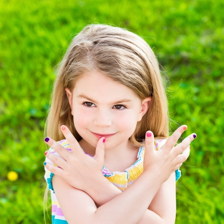 Beautiful smiling blond little girl with long hair and many-coloured manicure
