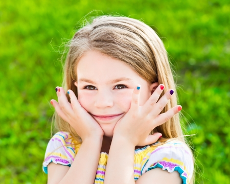 Adorable smiling blond little girl with long hair and many-coloured manicure
