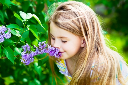Beautiful blond little girl with long hair smelling flower photo