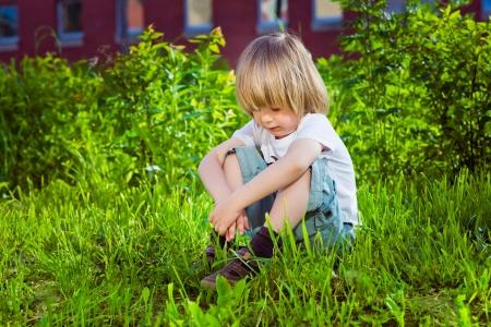 Portrait of a handsome sad little boy sitting on grass near his school