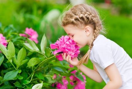 Hermosa niña rubia con el pelo largo con olor de flores Foto de archivo
