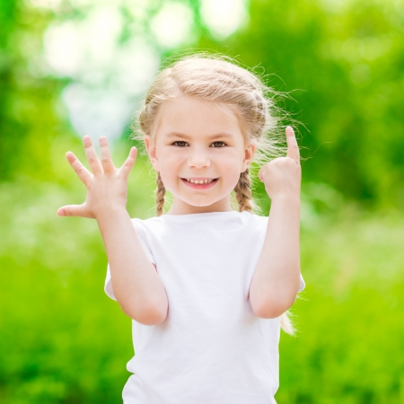 Beautiful blond little girl showing six fingers (her age) and smiling Banque d'images