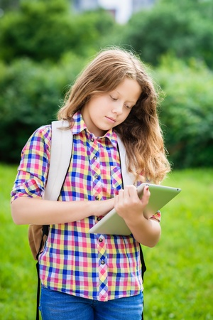 touch pad: Outdoor portrait of a beautiful teenager girl in casual clothes with backpack holding digital tablet in her hand, typing and reading