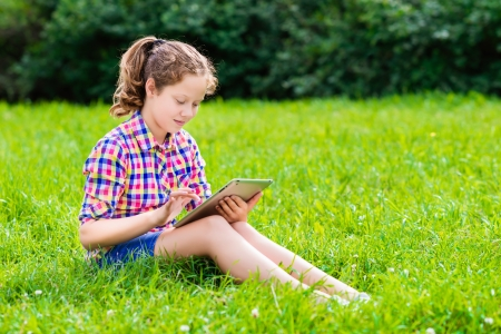 Outdoor portrait of a pretty teenager girl in casual clothes sitting on the grass with digital tablet on her knees, reading and surfing