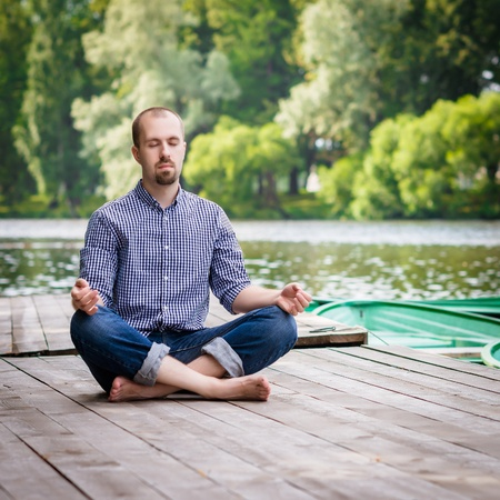 Young handsome bearded man sitting on wooden pier in summer day, meditating and relaxing