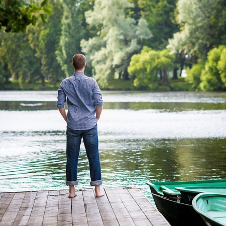 standing water: Young handsome man standing on wooden pier, relaxing and meditating in summer morning, back view