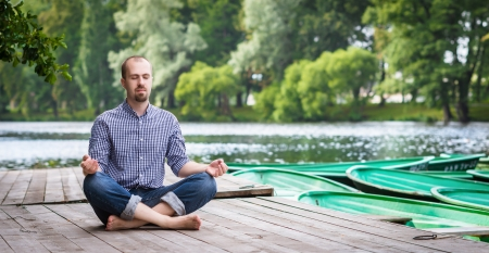 meditative: Young handsome bearded man with closed eyes sitting on wooden pier, relaxing and meditating in summer evening