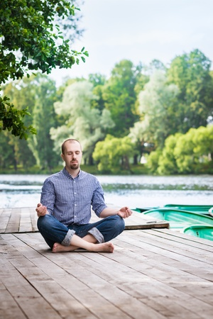 Young attractive breaded man with closed eyes sitting on wooden pier, relaxing and meditating in summer morning photo