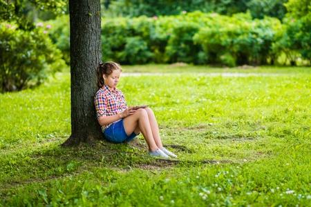 デジタル タブレットのツリーの下の公園で彼女の膝の上にカジュアルな服装でかなりティーンエイ ジャーの女の子