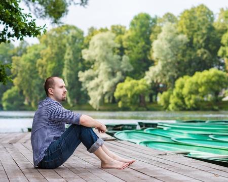 若いハンサムなひげを生やした男夏の日、木製の桟橋に座って瞑想とリラックス