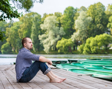 Young handsome bearded man sitting on wooden pier in summer day, meditating and relaxing Фото со стока - 21742200